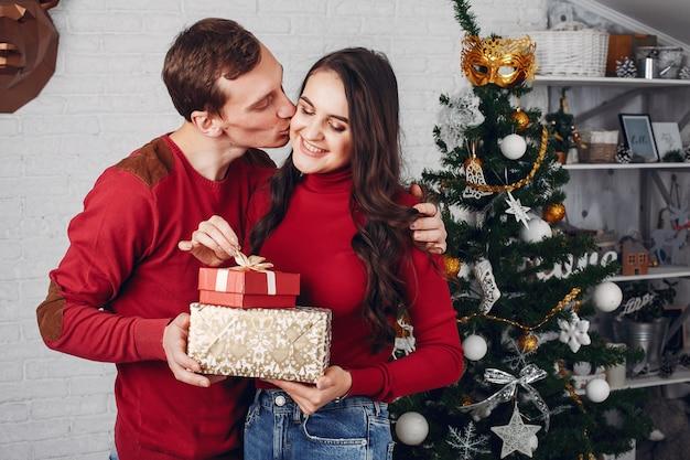 クリスマスツリーの近くに自宅でかわいい家族 無料写真