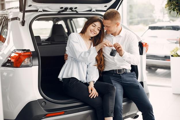 車のサロンでスタイリッシュでエレガントなカップル 無料写真