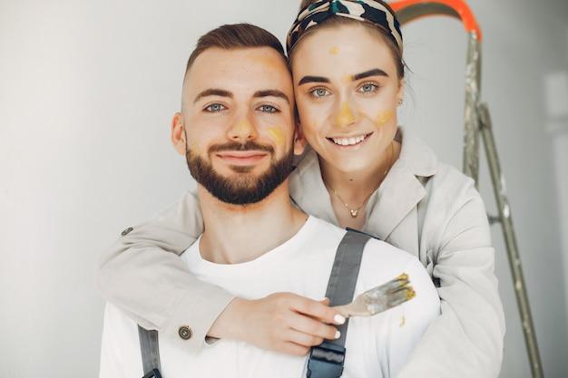 Молодая и милая пара ремонтирует комнату Бесплатные Фотографии