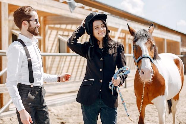 女の子と牧場で馬の隣に立っているエレガントな男 無料写真