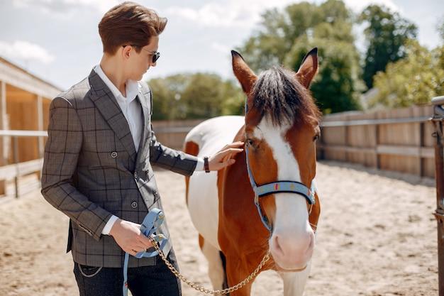 牧場で馬の隣に立っているエレガントな男 無料写真