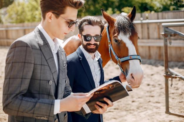 牧場で馬の隣に立っているエレガントな男性 無料写真