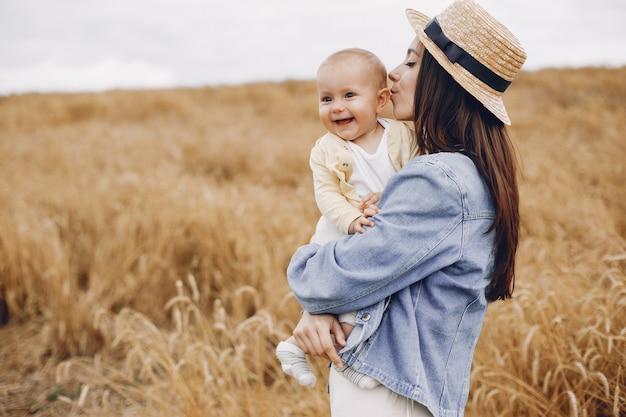 秋のフィールドで遊ぶ娘を持つ母 無料写真