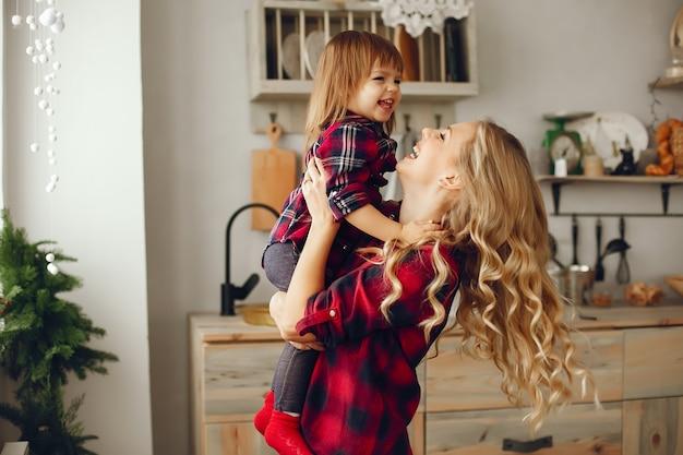 台所で小さな娘を持つ母 無料写真