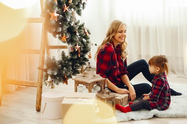 クリスマスツリーの近くに家で座っている家族 無料写真