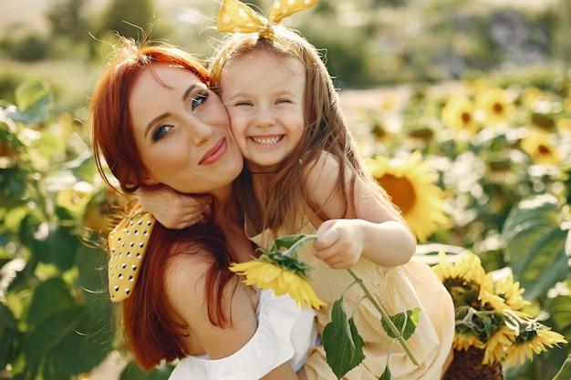 ひまわり畑で美しいとかわいい家族 無料写真
