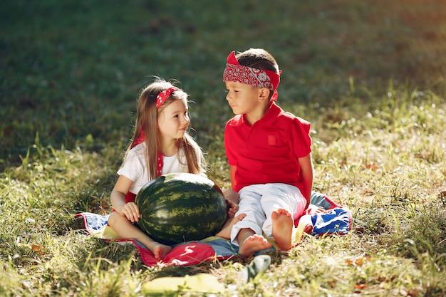 公園でスイカとかわいい小さな子供たち 無料写真