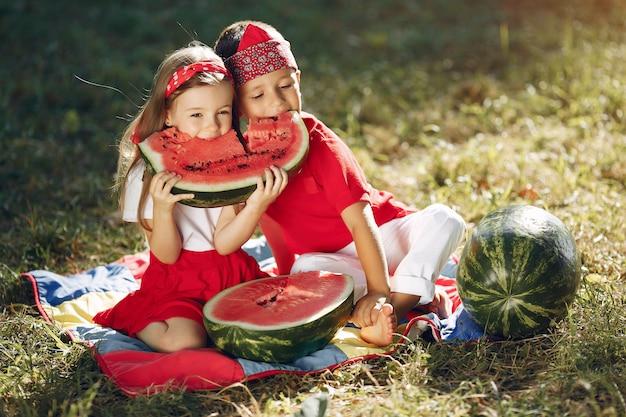 Симпатичные маленькие дети с арбузами в парке Бесплатные Фотографии