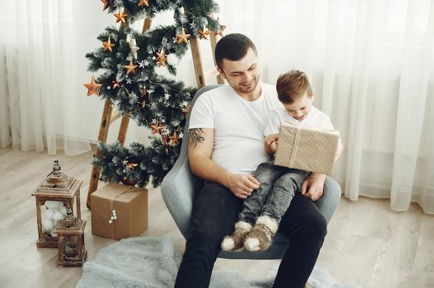 陽気な父と息子がクリスマスの装飾の近くに座っています。少年は喜びで座っています 無料写真
