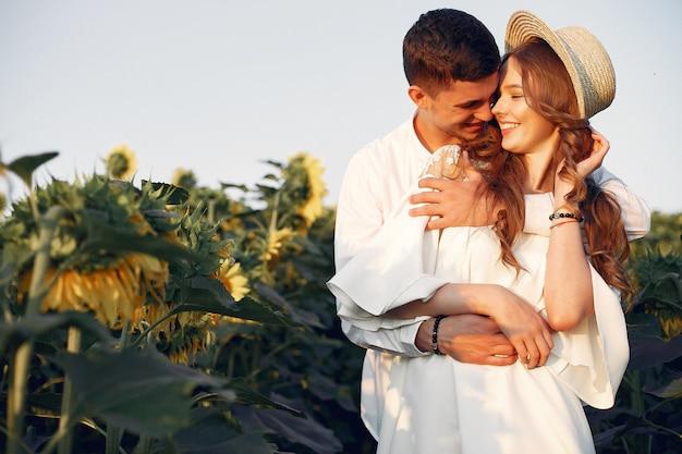 ひまわり畑で美しく、スタイリッシュなカップル 無料写真