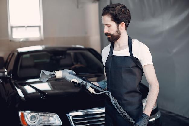 ガレージで彼の車を洗う人 無料写真