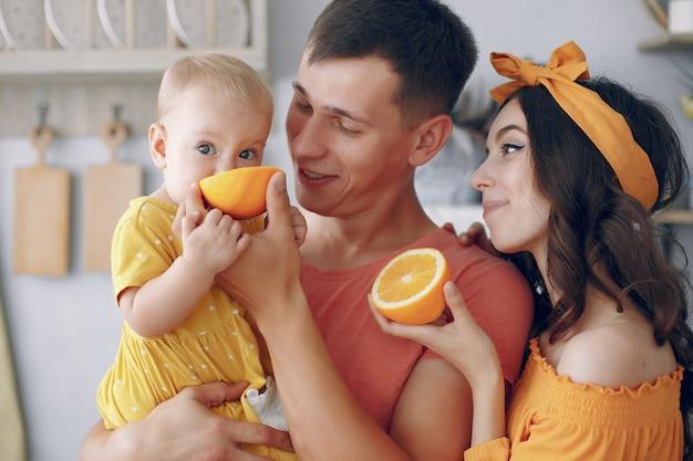 母と父は娘にオレンジを与えます 無料写真