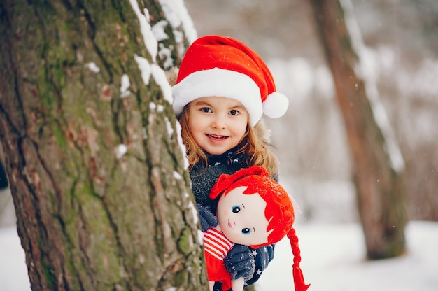 Маленькая девочка в синей шляпе играет в зимнем лесу Бесплатные Фотографии