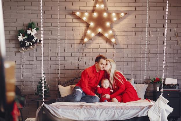 家族は自宅でベッドの上に座って 無料写真