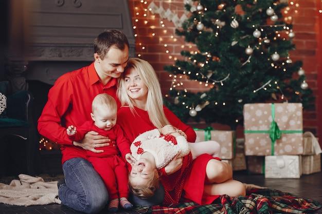 Семья сидит дома возле елки Бесплатные Фотографии