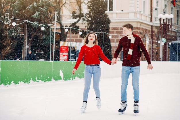 Милая пара в красных свитерах развлекается на ледовой арене Бесплатные Фотографии