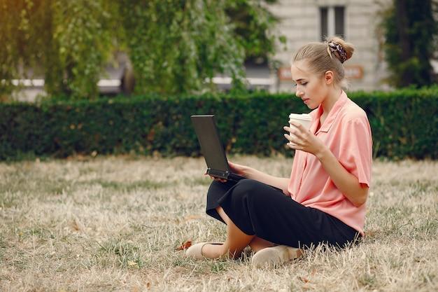 Девушка в розовой рубашке сидит в парке и пользуется ноутбуком Бесплатные Фотографии