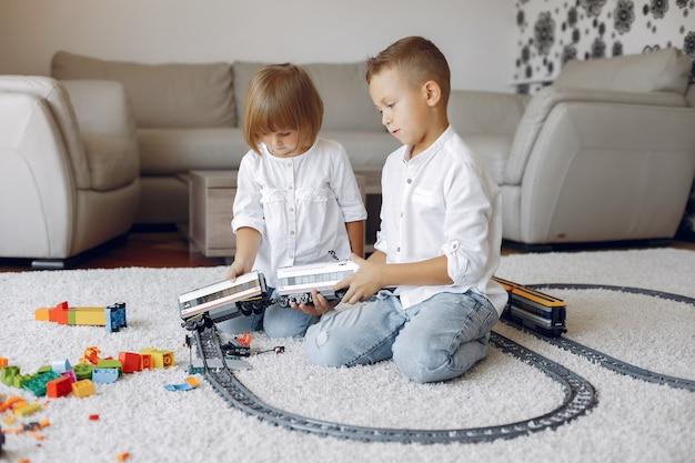 Дети играют с лего и игрушечным поездом в игровой комнате Бесплатные Фотографии