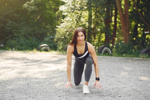 Спортивная девушка в чёрном топе тренируется в летнем парке Бесплатные Фотографии