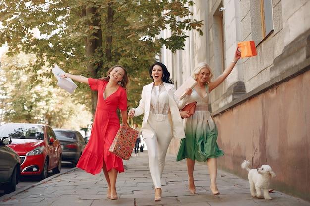 街で買い物袋を持つエレガントな女性 無料写真