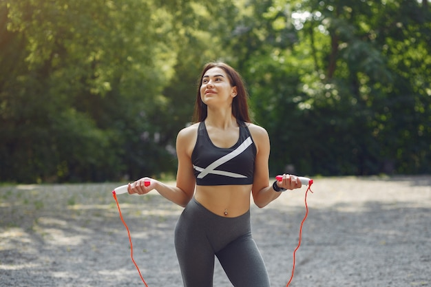 Спортивная тренировка девушки со скакалкой в летнем парке Бесплатные Фотографии