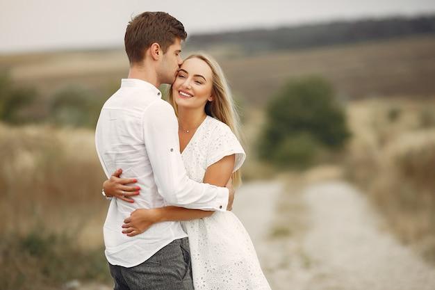 美しいカップルが秋のフィールドで時間を過ごす 無料写真