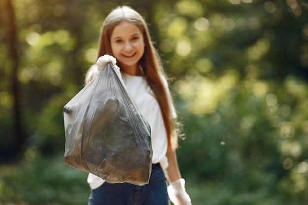 女の子は公園でゴミ袋にゴミを収集します 無料写真