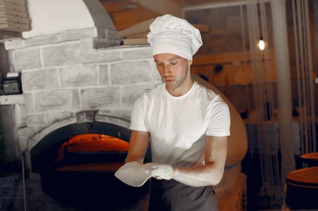 白い制服を着たシェフがピザを準備します 無料写真