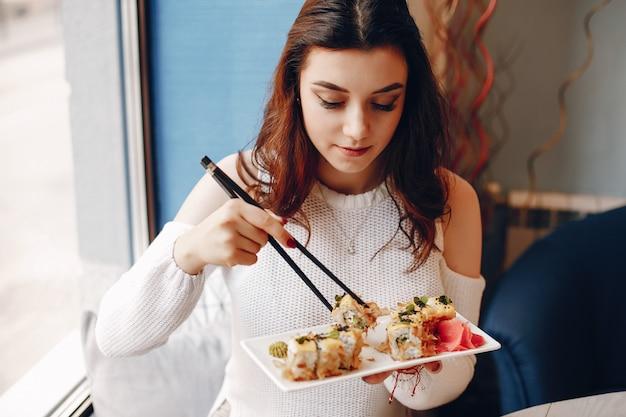テーブルに座って、カフェで寿司を食べる女性 無料写真