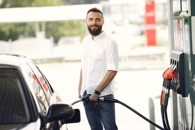 Красивый мужчина наливает бензин в бак автомобиля Бесплатные Фотографии