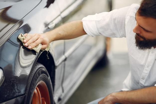 白いシャツを着た男が洗車で車を拭く 無料写真
