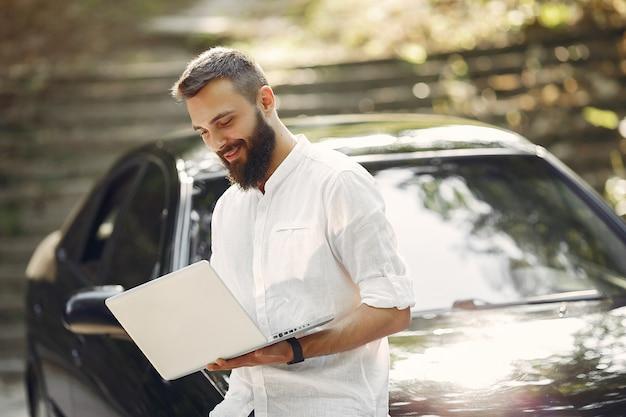 車の近くに立って、ラップトップを使用してスタイリッシュなビジネスマン 無料写真