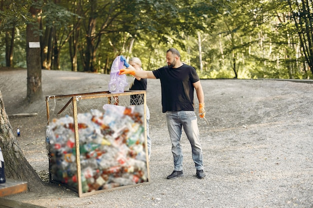 Пара собирает мусор в мешки для мусора в парке Бесплатные Фотографии