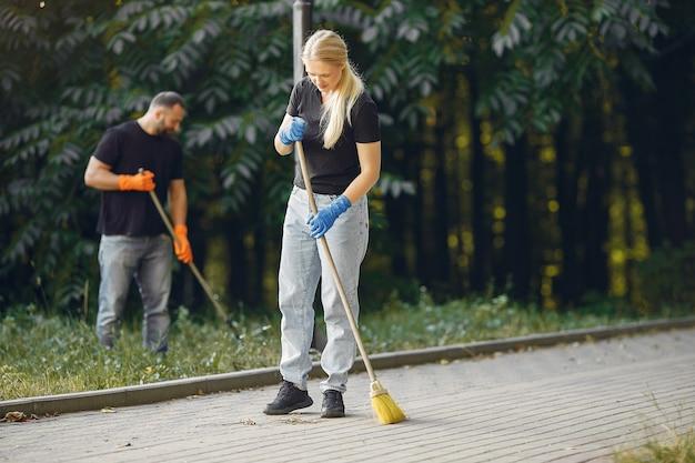 カップルが葉を集めて公園を掃除する 無料写真