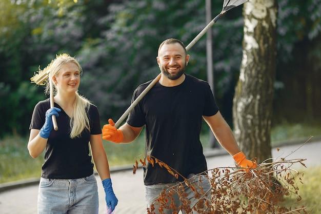 Пара собирает листья и убирает парк Бесплатные Фотографии