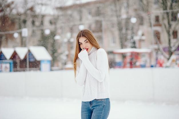 Молодая девушка в белом свитере стоит в зимнем парке Бесплатные Фотографии
