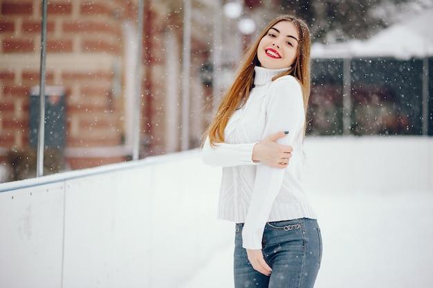 冬の公園に立っている白いセーターの少女 無料写真
