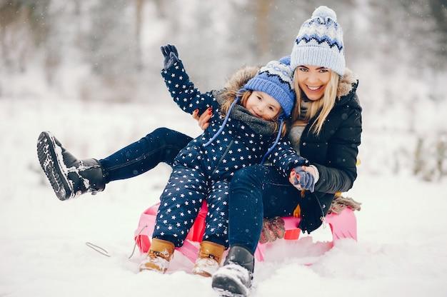 冬の公園で遊ぶ母と小さな女の子 無料写真