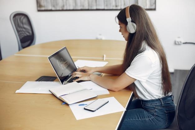 若い学生がテーブルに座ってラップトップを使用 無料写真
