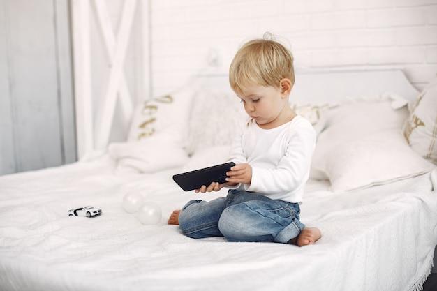 ベッドの上のノートパソコンで遊ぶかわいい男の子 無料写真