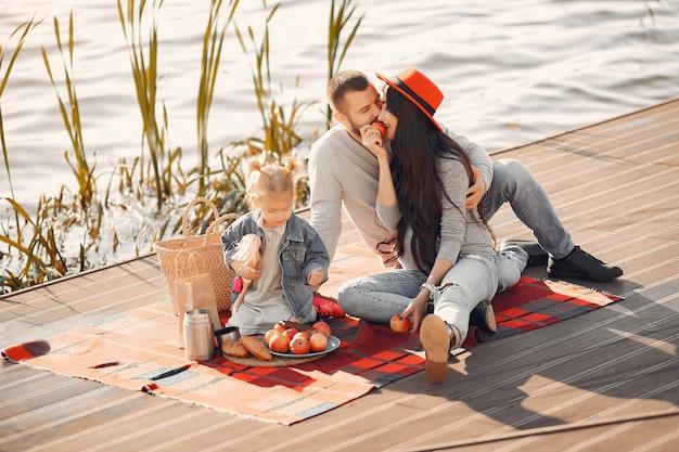 秋の公園で水の近くに座っている小さな娘と家族 無料写真