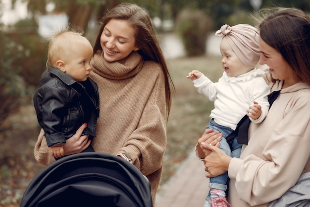 Две молодые мамы гуляют в осеннем парке с колясками Бесплатные Фотографии