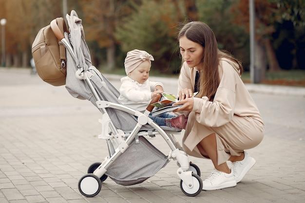 Молодая мама гуляет в осеннем парке с коляской Бесплатные Фотографии