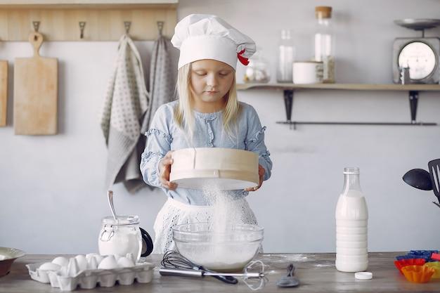 Маленькая девочка в белой шляпке готовит тесто для печенья Бесплатные Фотографии