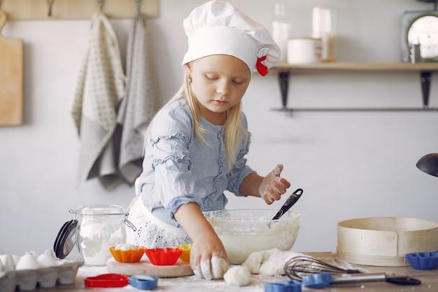 白いシェフの帽子の少女がクッキーの生地を調理します。 無料写真
