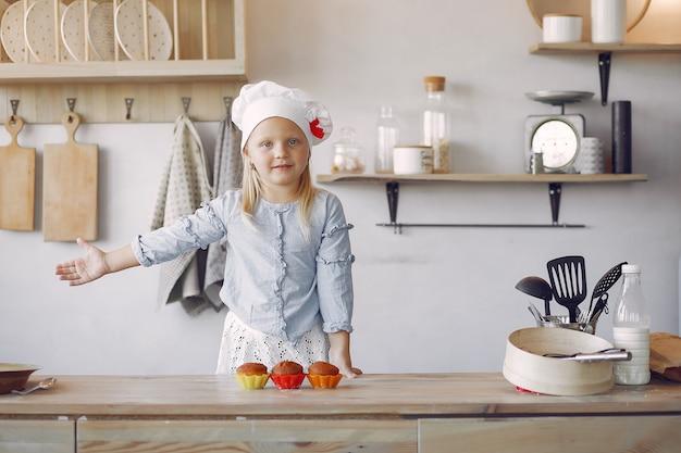 カップケーキとキッチンでかわいい女の子 無料写真