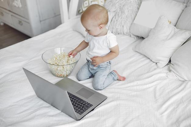 Милый маленький мальчик, играя с ноутбуком на кровати Бесплатные Фотографии