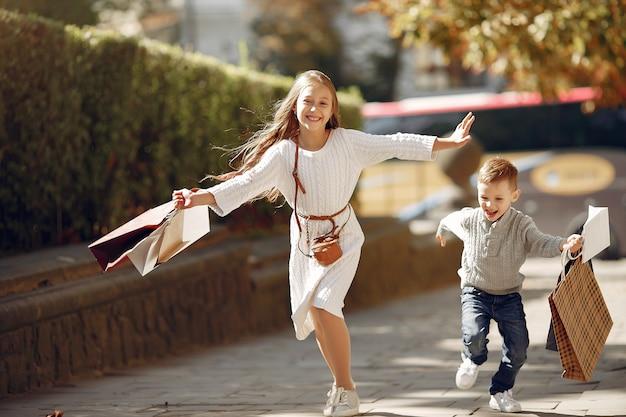 街で買い物袋を持つかわいい小さな子供 無料写真