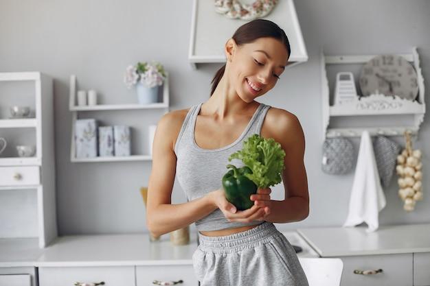 Красивая и спортивная женщина на кухне с овощами Бесплатные Фотографии