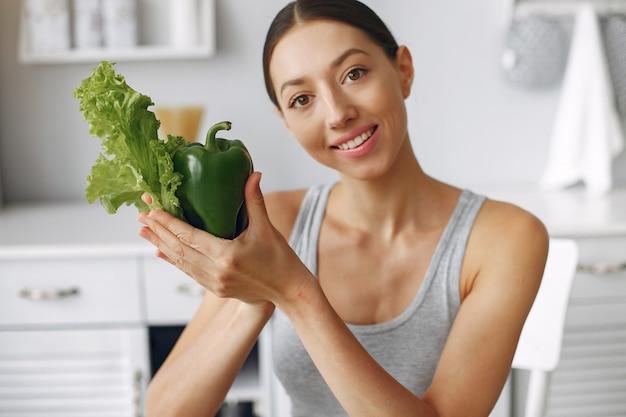野菜とキッチンで美しく、スポーティな女性 無料写真
